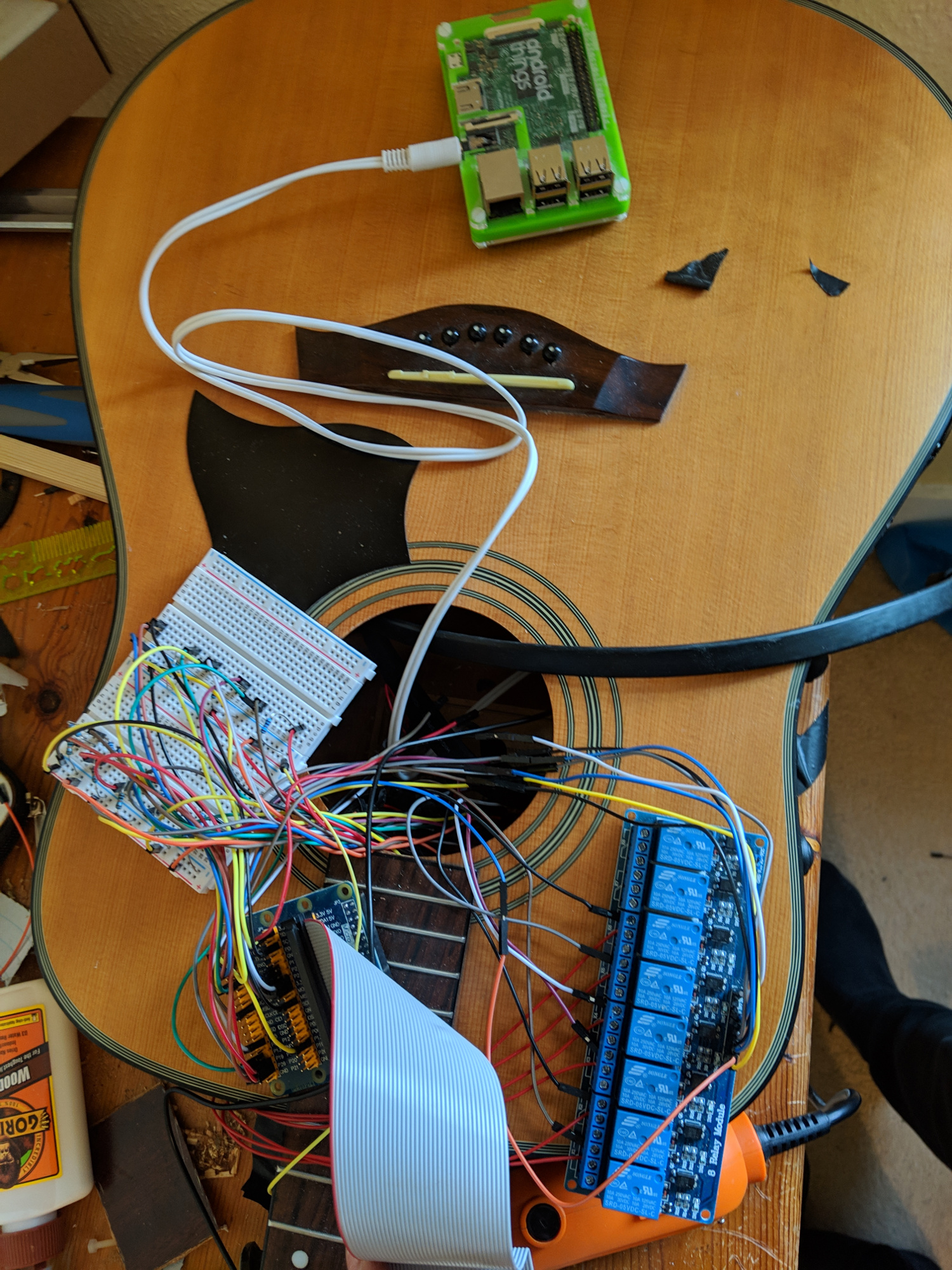 The Pi and other components, including an eight-channel relay for the solenoids in the Braille reader, are stuffed inside the body of the guitar