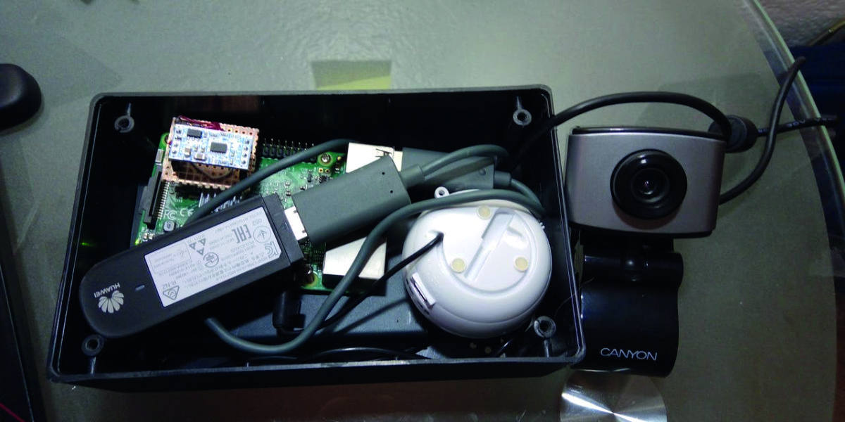 A Raspberry Pi, powered by a battery pack, is connected to the camera, speaker, an accelerometer, and mobile data dongle